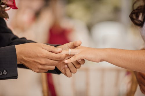 Side view of crop anonymous groom putting ring on finger of beloved during wedding ceremony