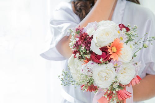 Crop unrecognizable bride in peignoir with blooming flower bouquet during festive event on white background