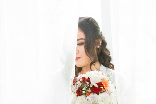 Crop dreamy woman with makeup and bright bridal bouquet looking away on white background