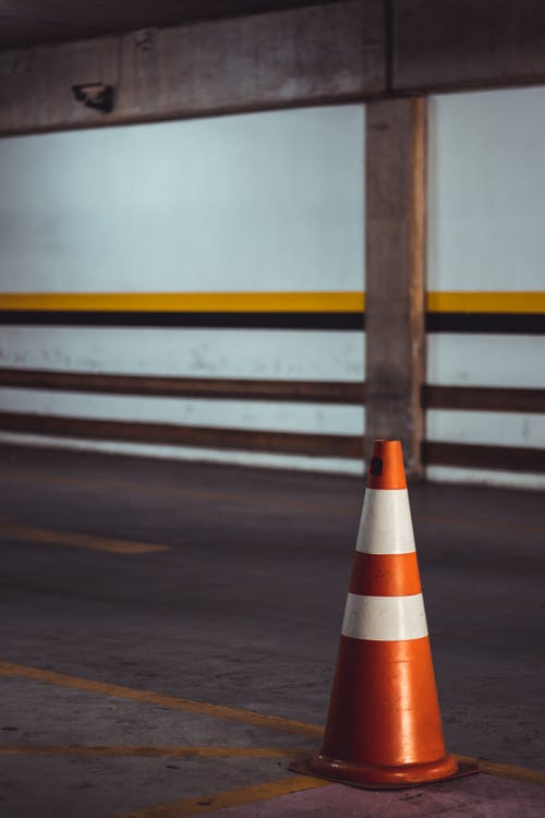 Orange and White Striped Traffic Cone On An Aspahlt Road