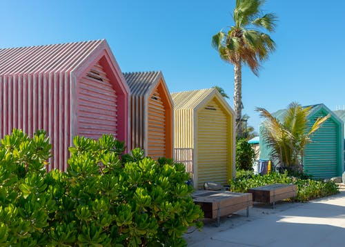 Colorful Beach Huts Near Green Trees Under Blue Sky