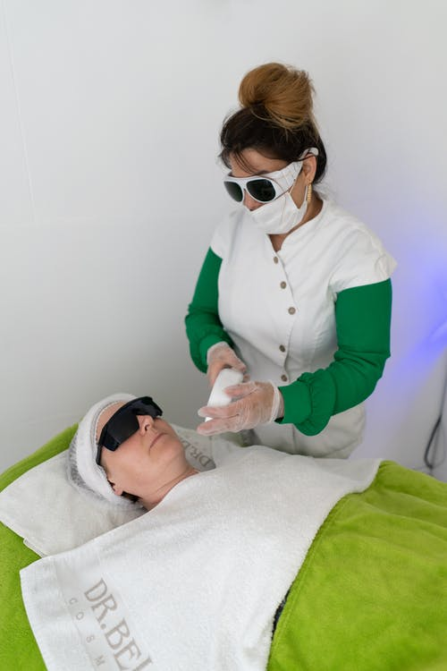 Woman in protective glasses and mask using laser for hair removal on face of client in beauty salon