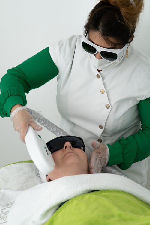 Focused professional cosmetician doing face skin care procedure for woman with professional equipment in clinic