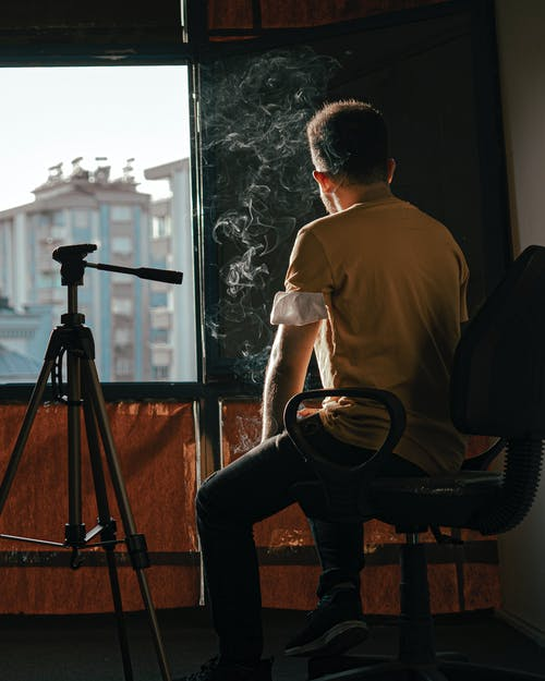 Man in White T-shirt and Blue Denim Jeans Sitting on Black Metal Tripod