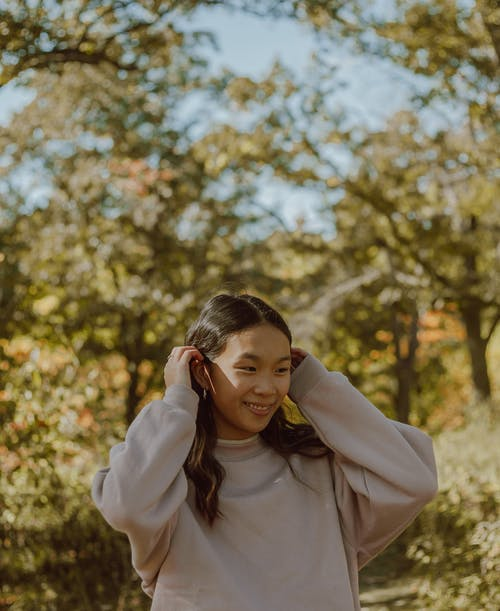 Positive young Asian lady smiling while chilling in autumn park