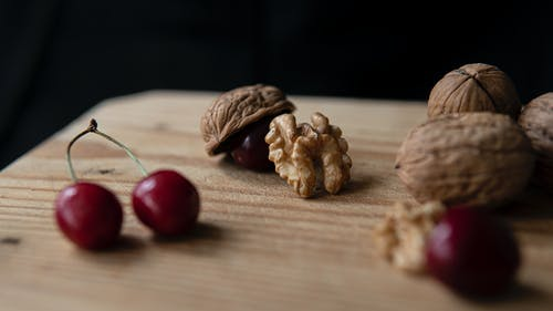 Crunchy walnuts and sweet cherries on cutting board