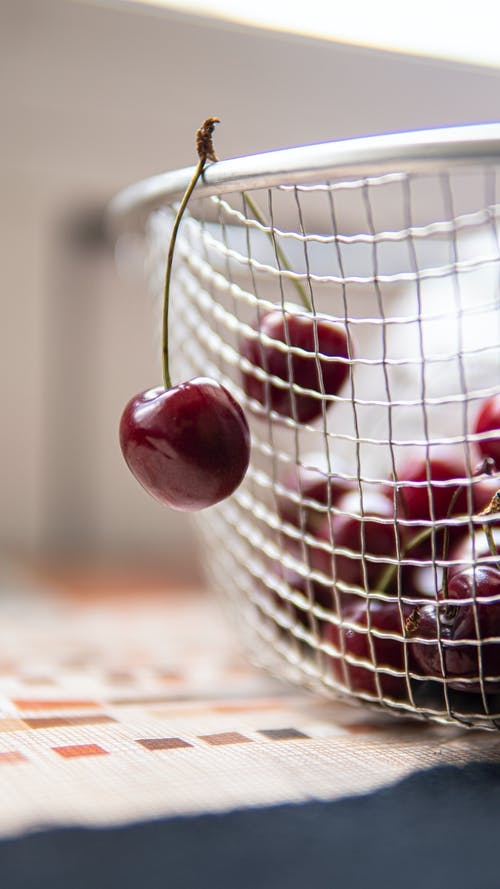 Delicious fresh cherries in colander in kitchen