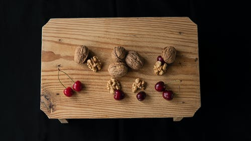 From above of crispy walnuts near sweet cherries on wooden table on black background