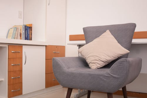 Gray Cushion Armchair Beside Brown Wooden Cabinet