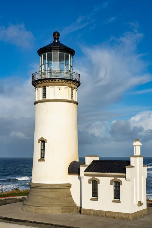 Cape Disappointment Lighthouse In Washington Under A Blue And Cloudy Sky