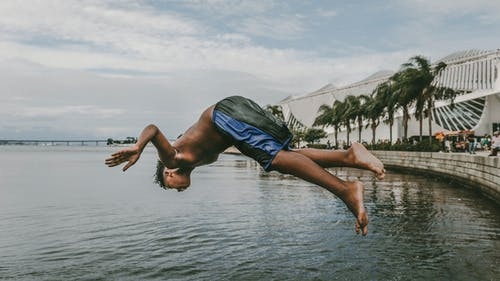 Man in Blue Shorts Jumping on Water