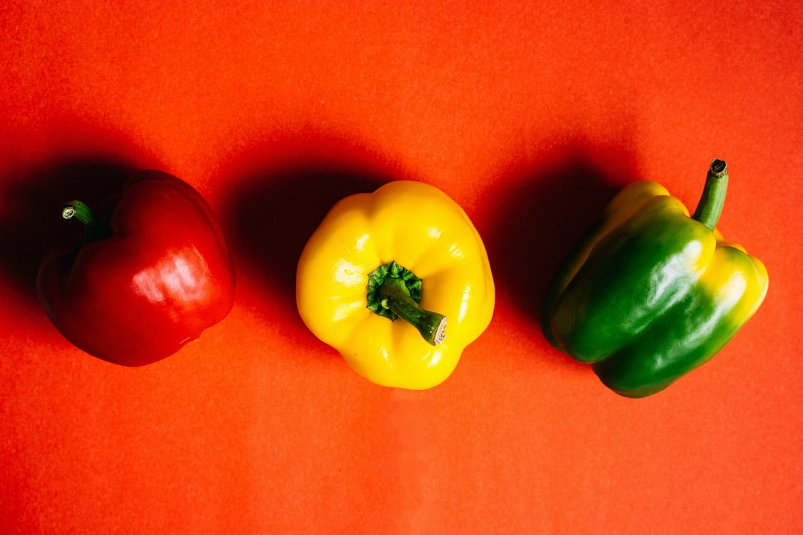 Close-Up Photo of Different Colors of Bell Peppers on Red Background
