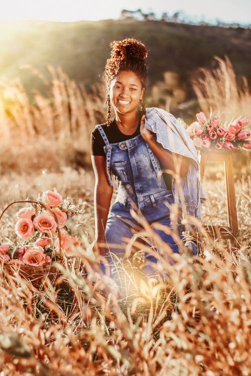 Woman in Blue Denim Vest and White Dress Sitting on Brown Grass Field