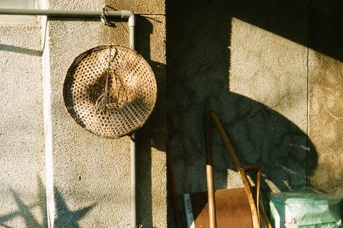 Straw hat hanging on pipe near concrete wall with shadow near junk yard in sunny weather in street in daylight