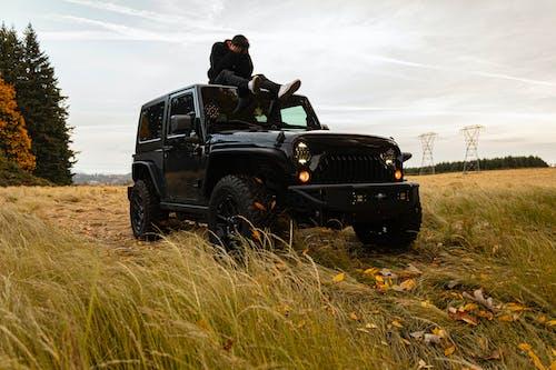 Man and Woman Kissing on Black Jeep Wrangler