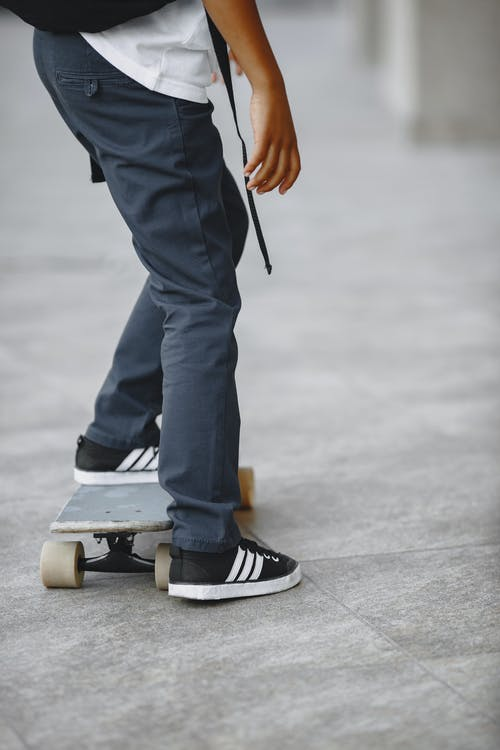 Person in Blue Denim Jeans and Black and White Sneakers Standing on Skateboard