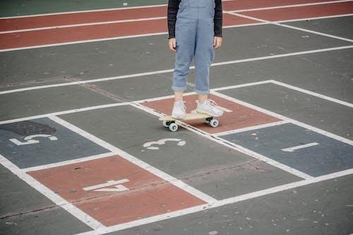 Crop kid riding skateboard on asphalt ground