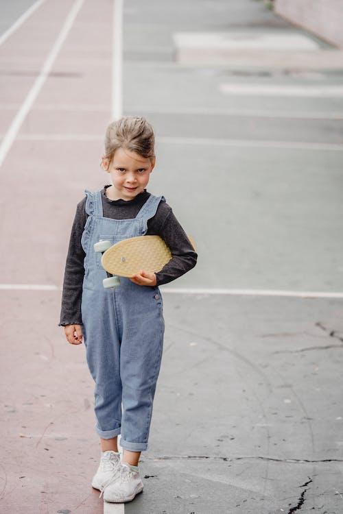 Cute little girl with skateboard on stadium