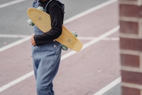 Crop kid with skateboard on schoolyard