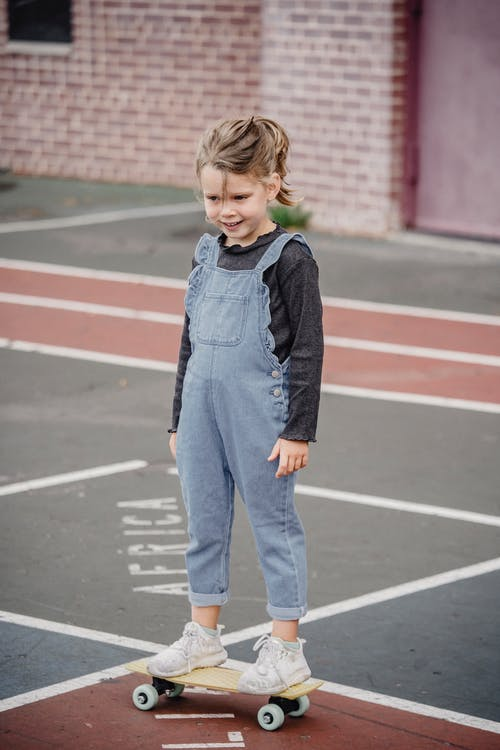 Cheerful preschool girl standing on skateboard