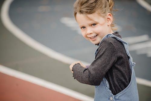 Cute little girl standing on stadium
