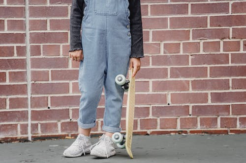 Crop kid with skateboard near brick building