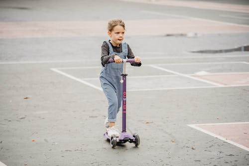 Cute kid on scooter in sports ground