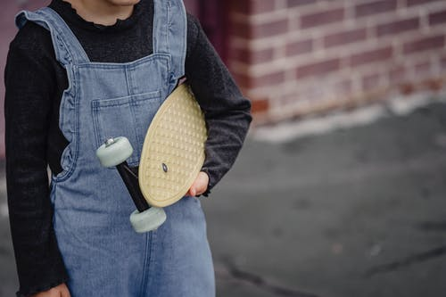 Crop child with penny board on street