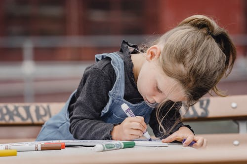 Adorable preschool girl in casual clothes sitting at table on schoolyard and holding marker while drawing illustration