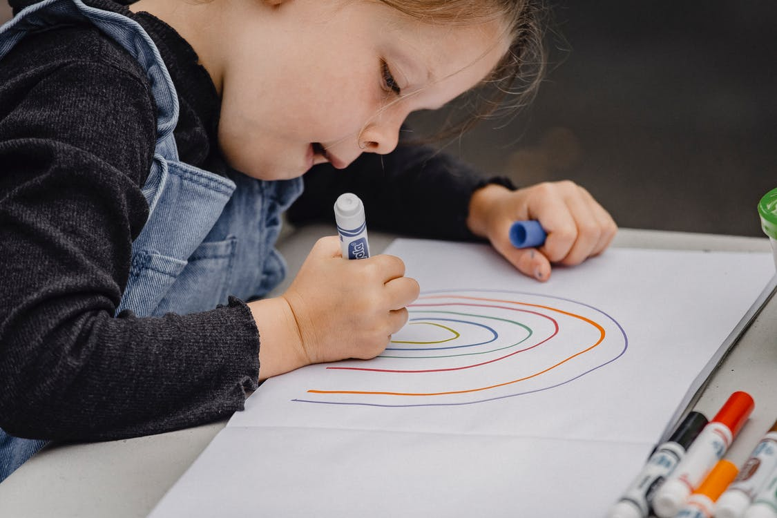 Little girl drawing rainbow on paper