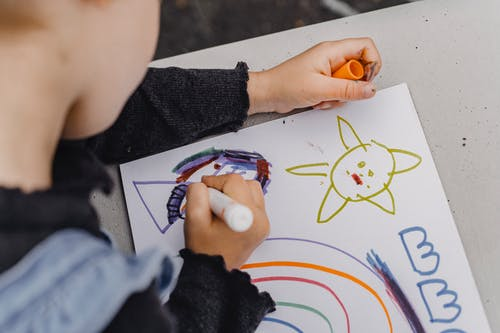 High angle of crop unrecognizable kid sitting at table and holding marker while painting colorful picture in album for drawing