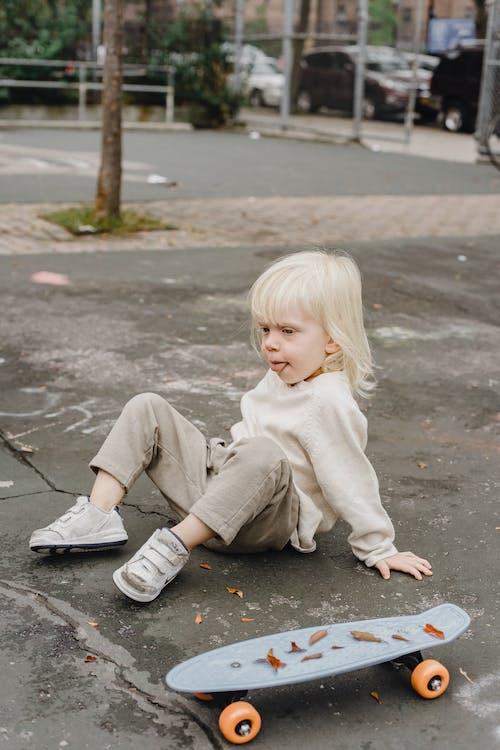 Little boy near skateboard on street