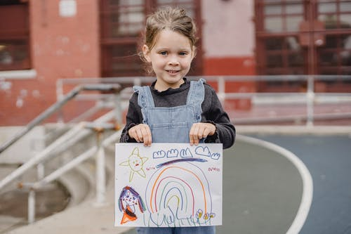 Happy little girl showing colorful drawing