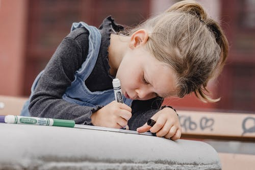 Focused little girl drawing with markers