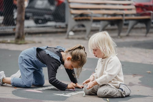 Focused little girls drawing on asphalt