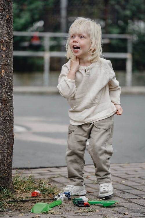 Full body adorable excited little girl in casual outfit standing near tree with toys and calling friend looking away