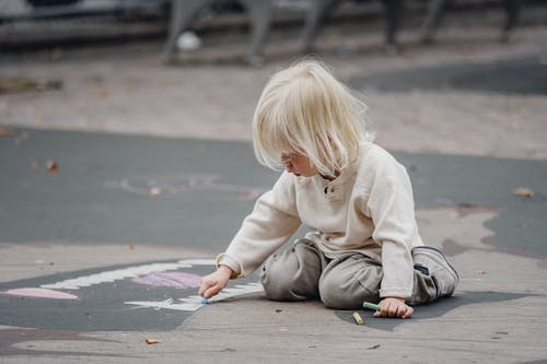 Focused child drawing with chalks