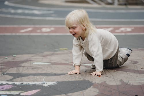 Cute girl sitting on asphalt