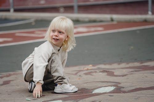 Happy little girl on asphalt ground