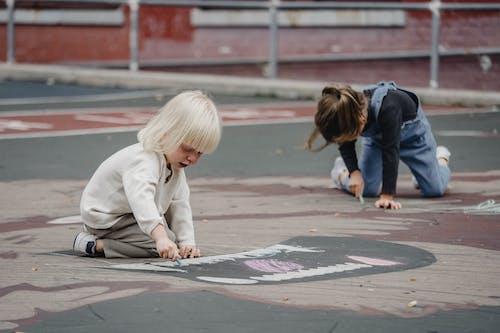 Little girls on asphalt with chalks