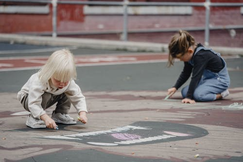Unrecognizable children drawing with chalks