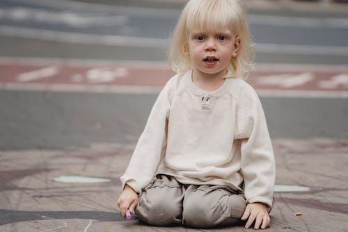 Funny little girl on asphalt