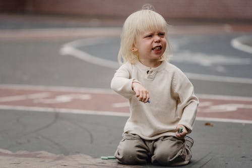 Full length dissatisfied little girl with chalks in casual wear sitting on asphalt ground and looking away