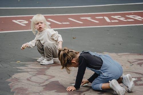 Cute kids drawing on asphalt