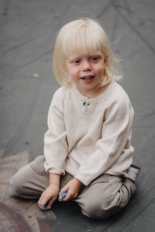 Adorable kid on asphalt ground