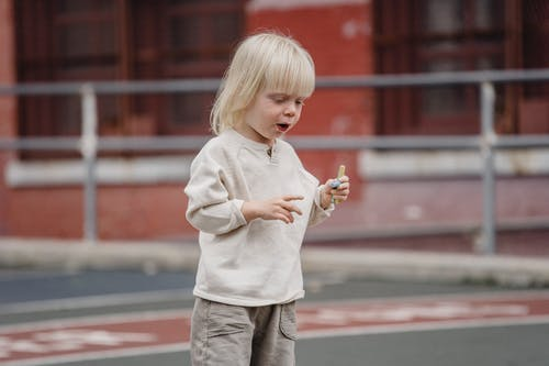 Cute little kid in casual wear standing on asphalt ground with chalks in hand and looking down ready to draw