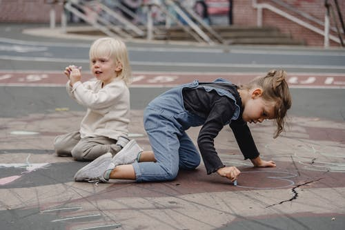 Concentrated kids with chalks on asphalt