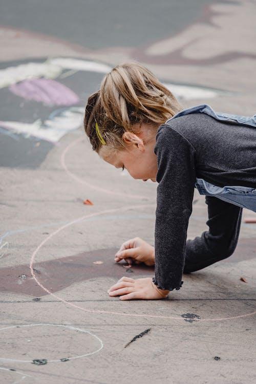 Cute child drawing on asphalt