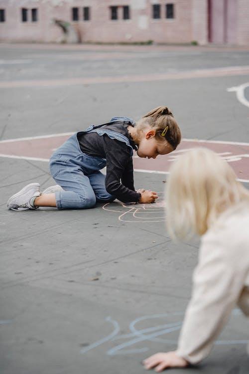 Girls drawing with chalks on asphalt