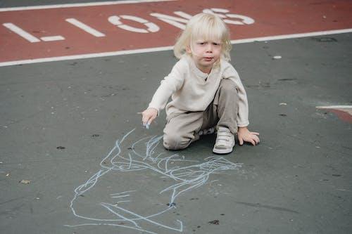 Adorable kid drawing on asphalt
